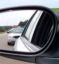 Police car in a car's rear view mirror